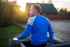 Attraktiver Mann, der auf Strand im Abendsonnenuntergang nach Sport sitzt Lizenzfreies Stockfoto