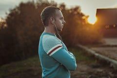 Attraktiver Mann, der auf Strand im Abendsonnenuntergang nach Sport sitzt Lizenzfreie Stockfotos
