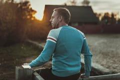 Attraktiver Mann, der auf Strand im Abendsonnenuntergang nach Sport sitzt Stockfotografie