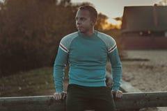 Attraktiver Mann, der auf Strand im Abendsonnenuntergang nach Sport sitzt Lizenzfreie Stockbilder