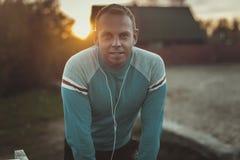 Attraktiver Mann, der auf Strand im Abendsonnenuntergang nach Sport sitzt Stockfotos