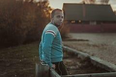 Attraktiver Mann, der auf Strand im Abendsonnenuntergang nach Sport sitzt Stockbild