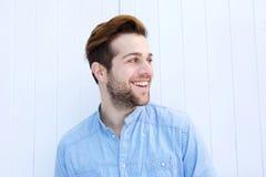 Attraktiver Mann, der auf weißem Hintergrund lächelt Stockfotos