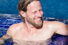 Attraktiver Mann, der in einem Pool sich entspannt Lizenzfreie Stockbilder