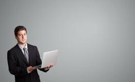 Attraktiver Mann, der einen Laptop hält und Kopienraum darstellt Stockbilder