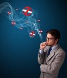 Attraktiver Mann, der gefährliche Zigarette mit Nichtraucherzeichen raucht Lizenzfreie Stockfotos