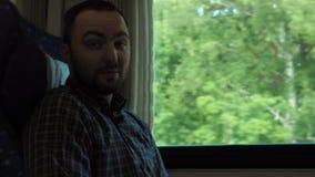 Attraktiver Mann, der mit Kamera beim Reiten eines Zugs spricht stock video
