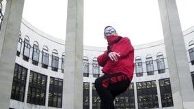 Attraktiver Mann in der roter Sportausstattung und -Sonnenbrille singt nahe bei Granitsäulen stock footage