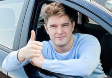 Attraktiver Mann, der in seinem Auto mit dem Daumen oben sitzt Stockfoto