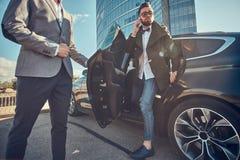 Attraktiver Mann in der Sonnenbrille spricht durch Smartphone und sitzt im Auto, w?hrend sein Assistent ?ffnende T?r f?r ihn ist lizenzfreie stockfotos