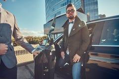 Attraktiver Mann in der Sonnenbrille spricht durch Smartphone und sitzt im Auto, w?hrend sein Assistent ?ffnende T?r f?r ihn ist stockbild