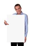 Attraktiver Mann, der unbelegtes weißes Zeichen anhält Lizenzfreie Stockfotos