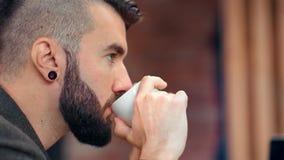 Attraktiver Mann des nachdenklichen Hippies der Nahaufnahme mit Duftkaffee-Holdingschale des Bartes denkender trinkender stock footage