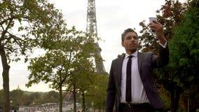 Attraktiver Mann in einer Klage nimmt ein selfie auf einem Smartphone nahe bei dem Eiffelturm stock video footage