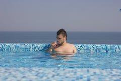 Attraktiver Mann im Pool mit einem Cocktail Stockbild