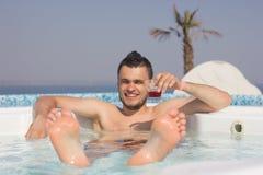 Attraktiver Mann im Pool mit einem Cocktail Lizenzfreies Stockfoto