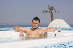 Attraktiver Mann im Pool mit einem Cocktail Stockbilder