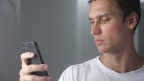 Attraktiver Mann Innen unter Verwendung des Smartphone, der Mitteilung auf dem Social Media lächelt sendet, modernen Lebensstil g stock footage