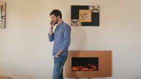 Attraktiver Mann mit Bart sprechend am Telefon im Raum stock video footage