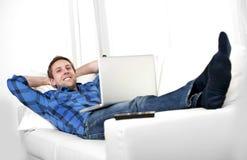 Attraktiver Mann mit dem Computer, der auf Couch sitzt Stockfotografie