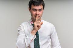 Attraktiver Mann mit dem Finger auf Lippen und Lippenstift am Hemdkragen Stockfoto