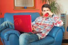 Attraktiver Mann mit trinkendem Kaffee des Laptops lizenzfreie stockfotos