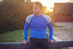 Attraktiver Mann steht auf Strand im Abendsonnenuntergang nach Sport Lizenzfreies Stockfoto