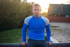 Attraktiver Mann steht auf Strand im Abendsonnenuntergang nach Sport Lizenzfreie Stockfotos