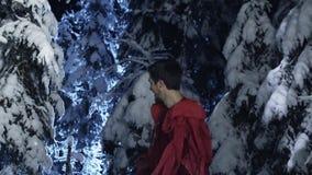 Attraktiver Mann und weibliche in den roten Kostümen haben Spaß im Holz des verschneiten Winters stock video