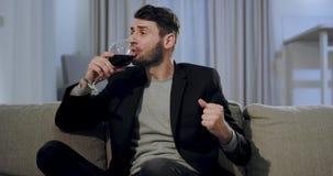 attraktiver Mann vor dem Fernsehen nach der Arbeit nimmt er ein Glas Wein und Aufpassen eines Films zu schauen zur Kamera stock footage