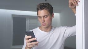Attraktiver Mann zu Hause unter Verwendung des Smartphone, der Mitteilung auf dem Social Media lächelt sendet, modernen Lebenssti stock video