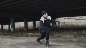 Attraktiver Mannläufer, der Übung für Morgengymnastik ausdehnend tut und am städtischen Standort im Winter draußen rüttelnd stock footage