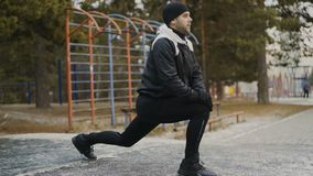 Attraktiver Mannläufer, der die Übung ausdehnend sich vorbereitet für Morgengymnastik und rüttelt im Winterpark tut stock footage