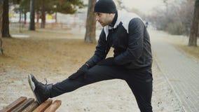 Attraktiver Mannläufer, der die Übung ausdehnend sich vorbereitet für Morgengymnastik und rüttelt im Winterpark tut stock video footage