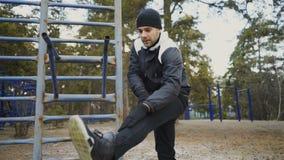 Attraktiver Mannläufer, der die Übung ausdehnend sich vorbereitet für Morgengymnastik und rüttelt im Winterpark tut stock video