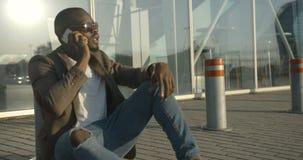 Attraktiver moderner afrikanischer Mann mit Sonnenbrille spricht über den Handy beim Sitzen auf der Straße und an sich lehnen stock footage