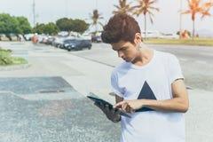 Attraktiver moderner junger weißer Mann unter Verwendung der Tablette nahe Seepromenade stockfotografie