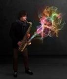 Attraktiver Musiker, der auf Saxophon mit bunter Zusammenfassung spielt lizenzfreie stockfotos