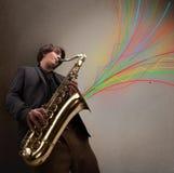 Attraktiver Musiker, der auf Saxophon während bunte Zusammenfassung spielt Stockbilder