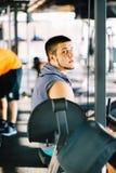 Attraktiver muskulöser Bodybuilder, der Pause von den Übungen mit Barbell in einer Turnhalle macht Kerlbodybuilder ermüdet in der Stockfotografie