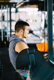Attraktiver muskulöser Bodybuilder, der Pause von den Übungen mit Barbell in einer Turnhalle macht Kerlbodybuilder ermüdet in der Lizenzfreie Stockfotos