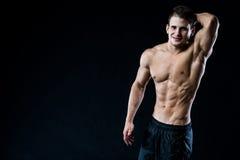 Attraktiver muskulöser junger Mann, der zur Kamera schaut und mit dem Arm oben, Hand hinter Kopf, auf Schwarzem lächelt Lizenzfreie Stockbilder