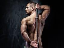 Attraktiver muskulöser Mann, der mit Klinge aufwirft. Stockfotografie