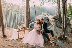 Attraktiver Paarjungvermählten-, glücklicher und frohermoment Mann und Frau in der festlichen Kleidung sitzen auf den Steinen nah Lizenzfreies Stockfoto