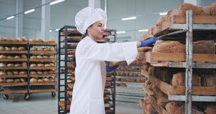 Attraktiver Platz des Frauenbäckers sehr auf dem Auftrag das frische gebackene Brot sie tragende stilvolle Uniform für Bäcker stock footage