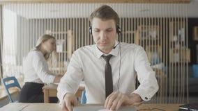 Attraktiver positiver junger Mann kam zum Call-Center-B?ro und beginnt Arbeit stock footage