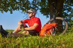 Attraktiver Radfahrer im Sturzhelm, der auf der grünen Wiese nahe dem Zyklus in der Landschaft sitzt Stockbild