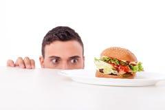Attraktiver recht junger Mann hat sehr Hunger Lizenzfreies Stockfoto