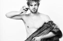 Attraktiver reicher Aufstellungspelzmantel des Kerls auf nacktem Körper Reicher Athlet genießen sein Leben Reichtum und Luxuskonz lizenzfreies stockbild