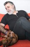 Attraktiver Senior mit dem weißen Bart, der mit Dachshundhund spielt Stockbild